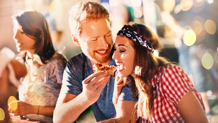 Man and a woman are sitting at a table with friends. Man is feeding the woman a slice of pizza.