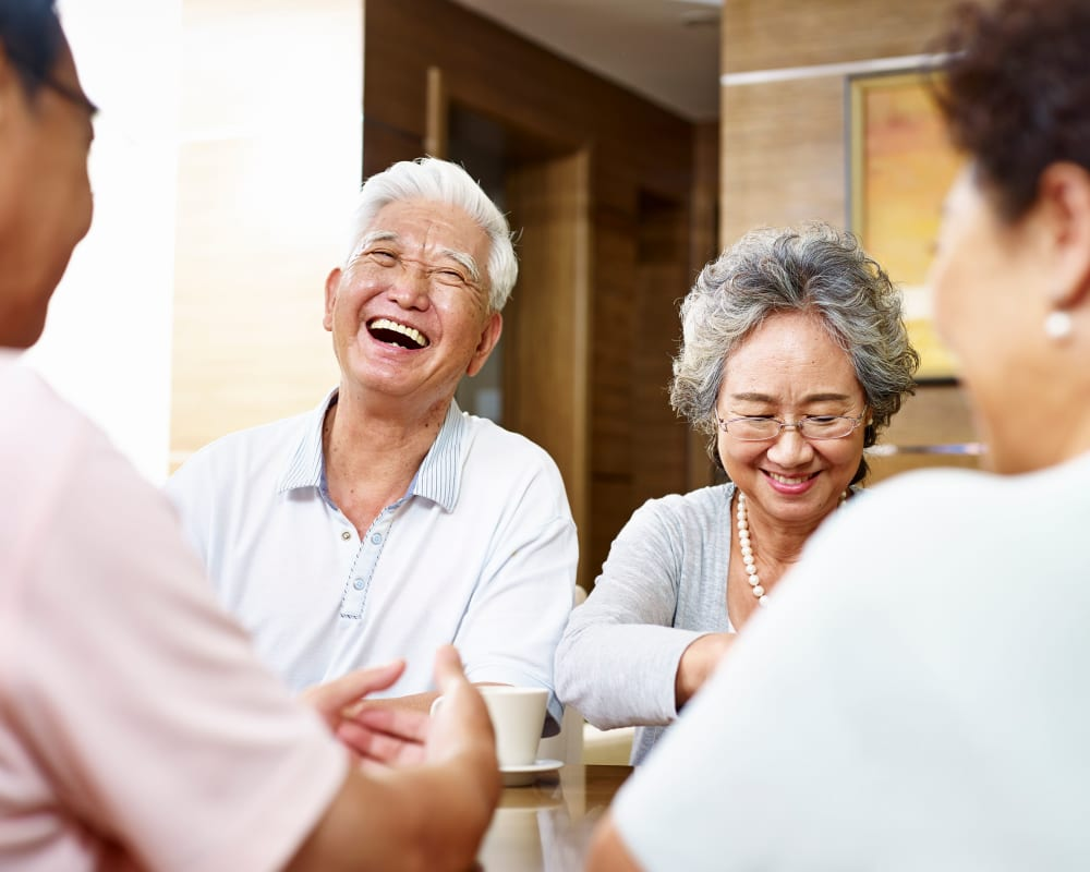 A resident couple laughing with their friends at RiverView Ridge in Rock Valley, Iowa.