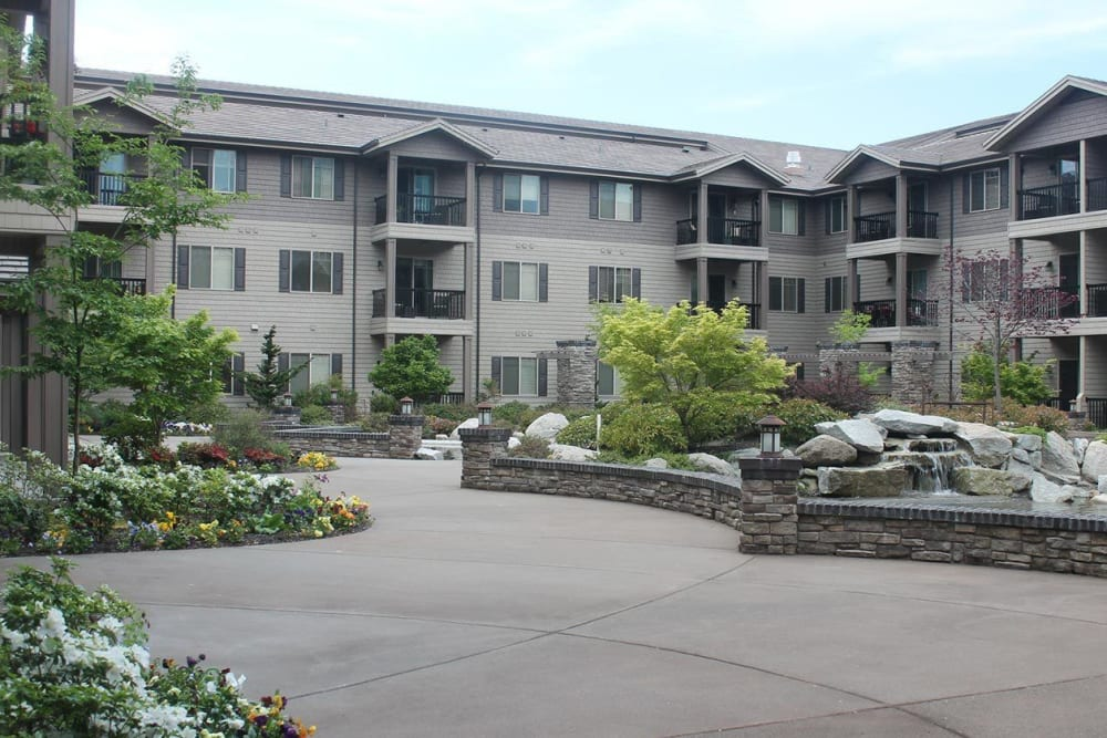 Front entrance to upscale senior living facility with stonework, pond, and foliage at The Springs at Veranda Park in Medford, Oregon