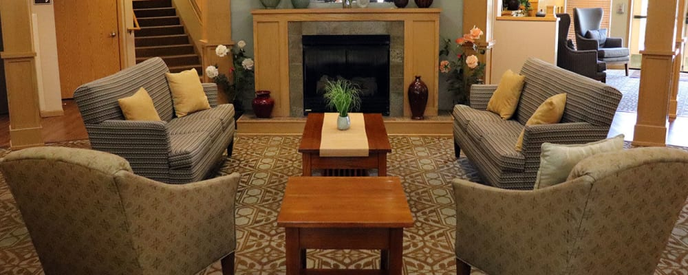 Welcoming upscale lounge seating with comfy armchairs,  flowers and fireplace at The Springs at Sunnyview in Salem, Oregon