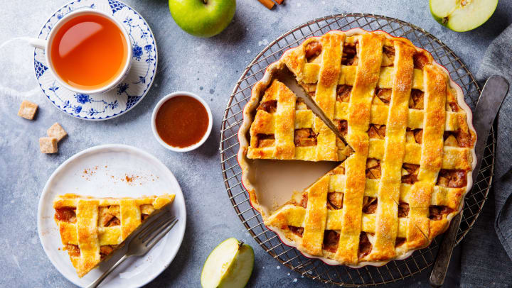 Apple pie on a cooling rack, on a table, with a slice cut out, sitting next to various ingredients and a cup of tea.