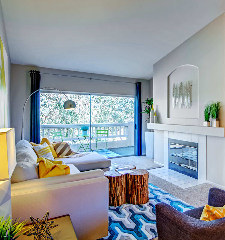 Modern furnishings, plush carpeting, and a fireplace in a model home at Sofi Canyon Hills in San Diego, California