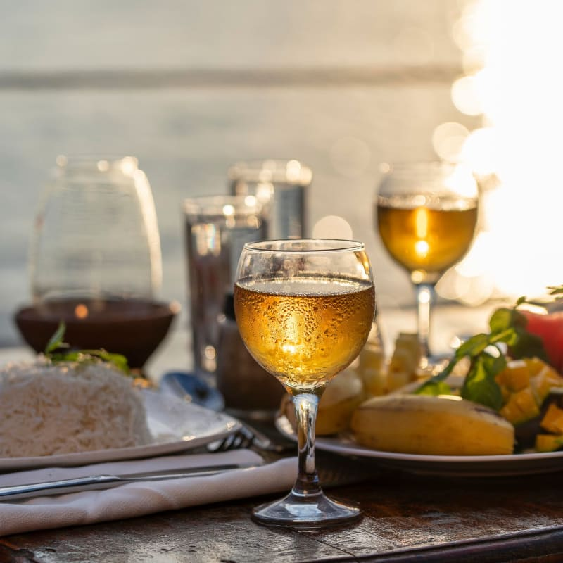 Table with a delicious meal and glasses of wine at sunset at a restaurant at Portside Ventura Harbor in Ventura, California