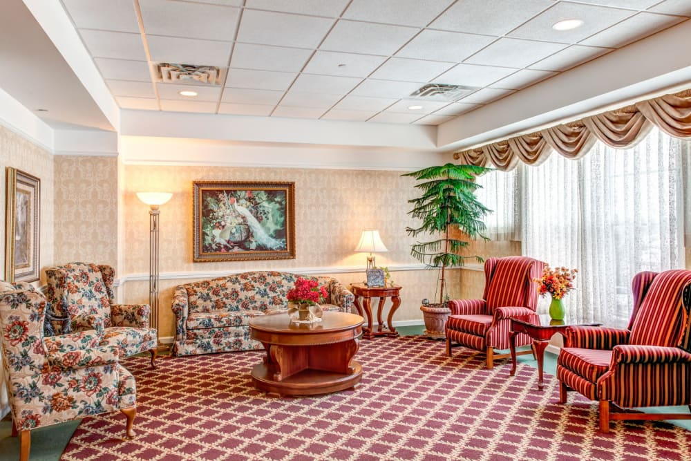 Cheerful red communal living room area complete with paintings and foliage at Grand Victorian of Rockford in Rockford, Illinois