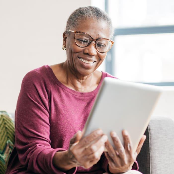 Resident enjoys social media in her apartment at The Preserve of Roseville in Roseville, Minnesota.