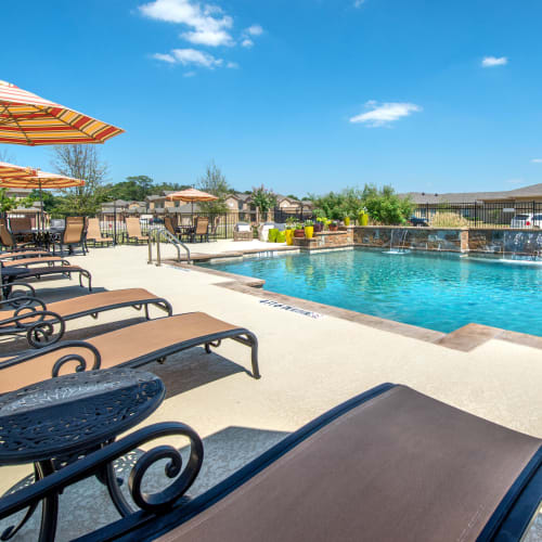Chaise lounge chairs flanking the pool on a beautiful day at Olympus Willow Park in Willow Park, Texas