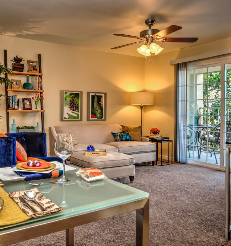 Ceiling fan and plush carpeting in the living area of a model senior apartment at Bella Vista Senior Living in Mesa, Arizona
