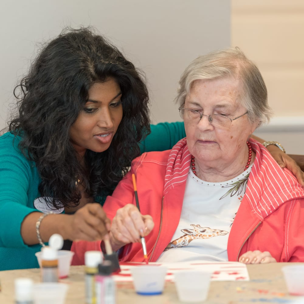 Team member and resident painting together at Inspired Living Lewisville in Lewisville, Texas