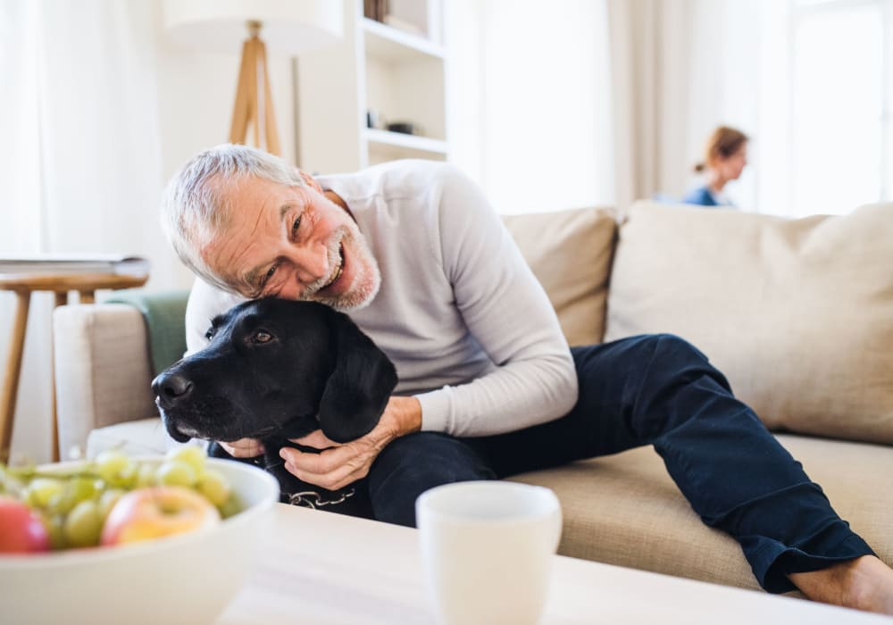 Man petting his dog on the couch at Fairbrooke Senior Apartments in Aberdeen, Maryland