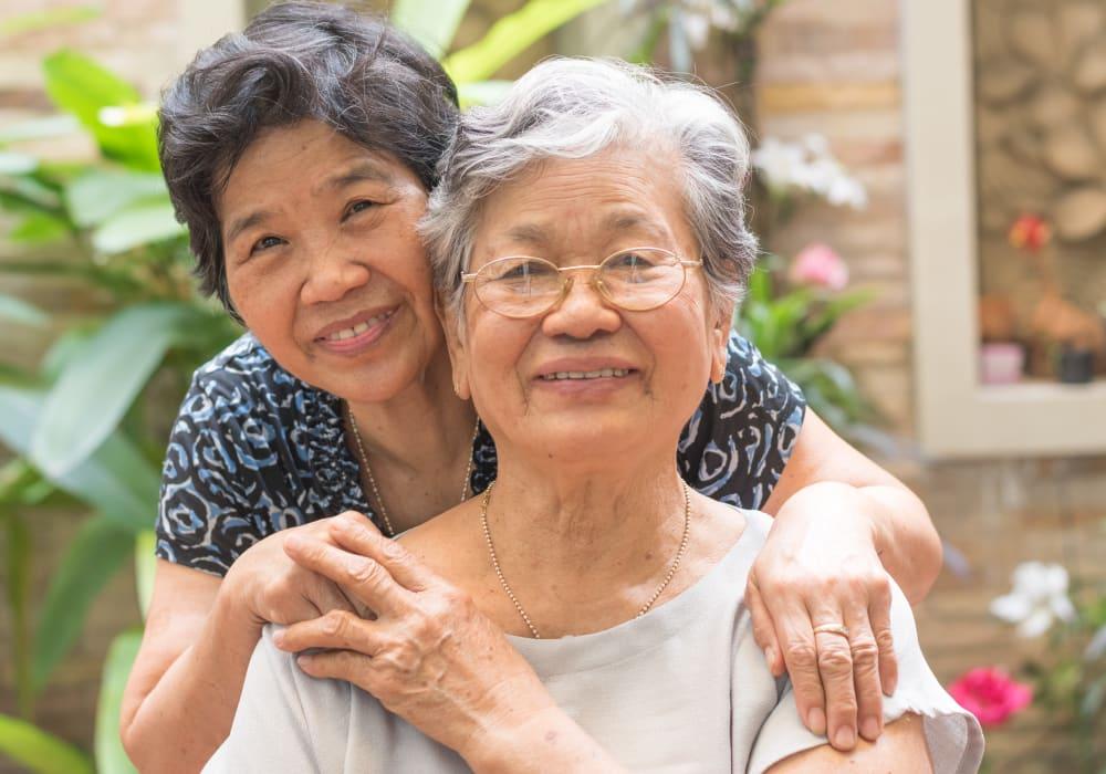 Resident friends hugging at Holden Southcenter in Tukwila, Washington.