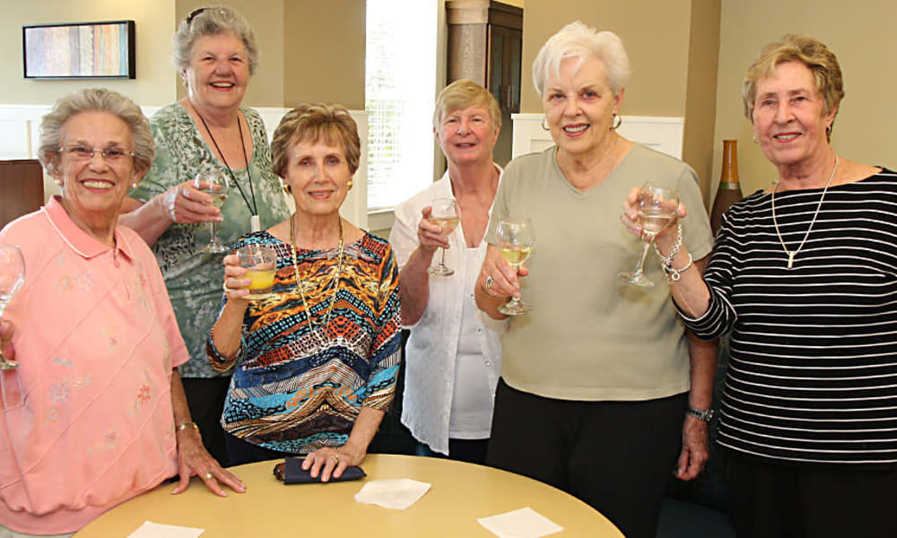 Group of 6 seniors toasting at an event in MacArthur Hills in Irving, Texas
