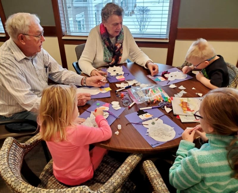 Residents and children doing arts and crafts together at Arbor Glen Senior Living in Lake Elmo, Minnesota