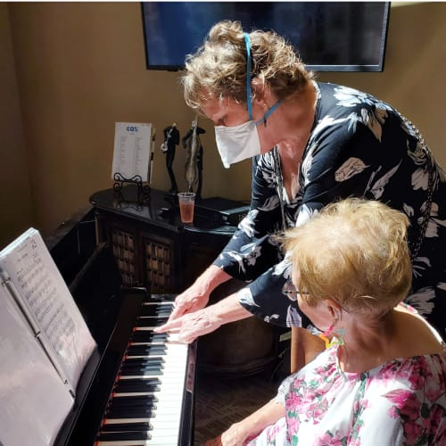 Team member with resident at the piano at The Oxford Grand Assisted Living & Memory Care in Wichita, Kansas