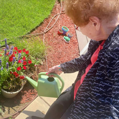 Resident watering the garden at The Oxford Grand Assisted Living & Memory Care in Wichita, Kansas