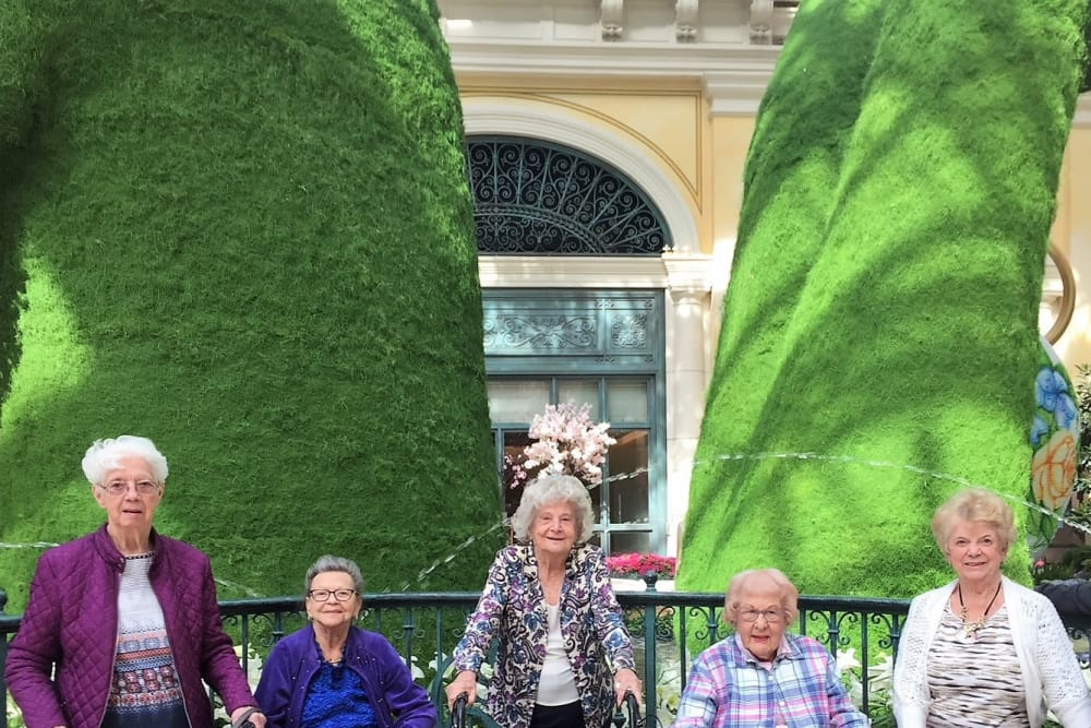 senior residents taking a photo in front of trees