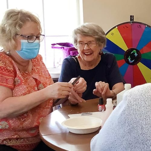 Masked caretaker doing resident nails at Canoe Brook Assisted Living in Duncan, Oklahoma