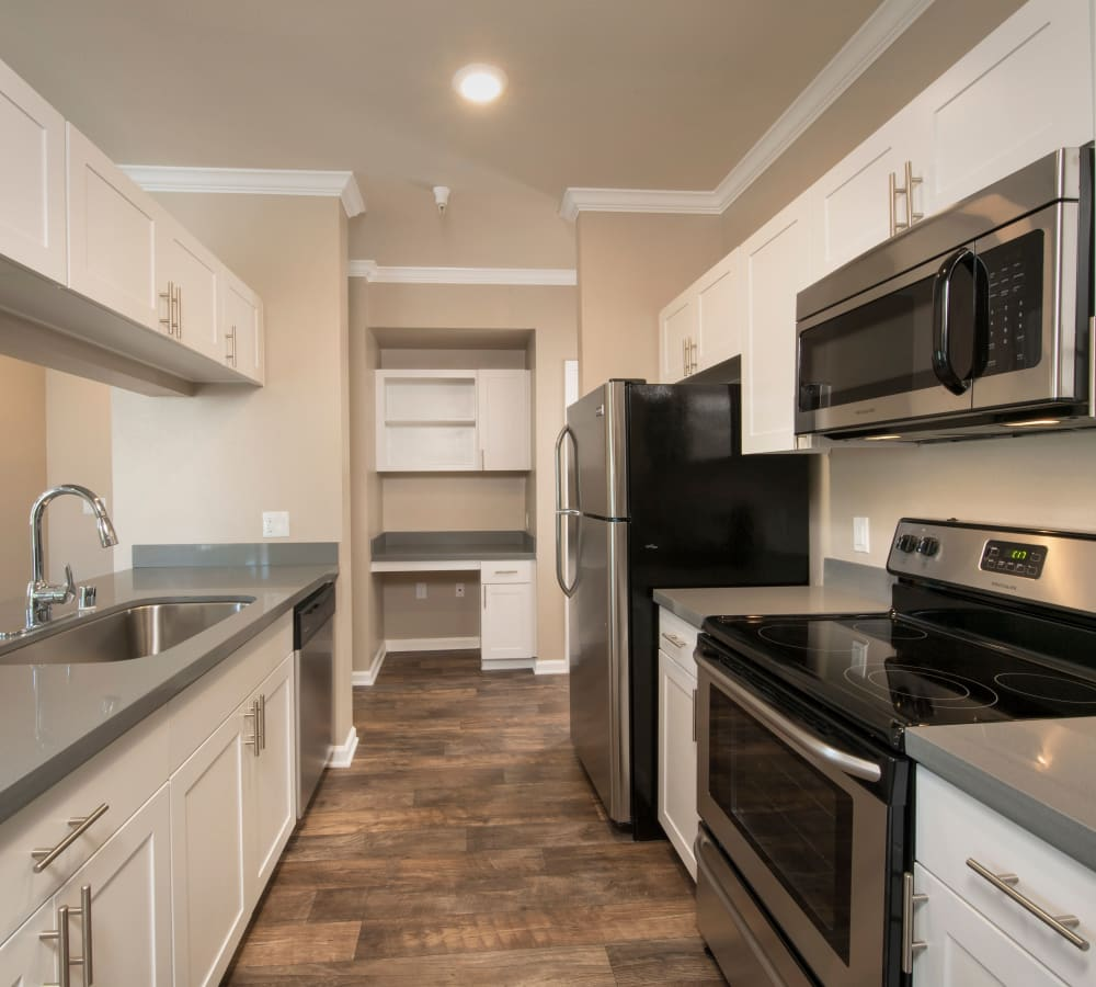 A luxury kitchen with stainless-steel appliances and a glass-top oven at Esplanade Apartment Homes in Riverside, California
