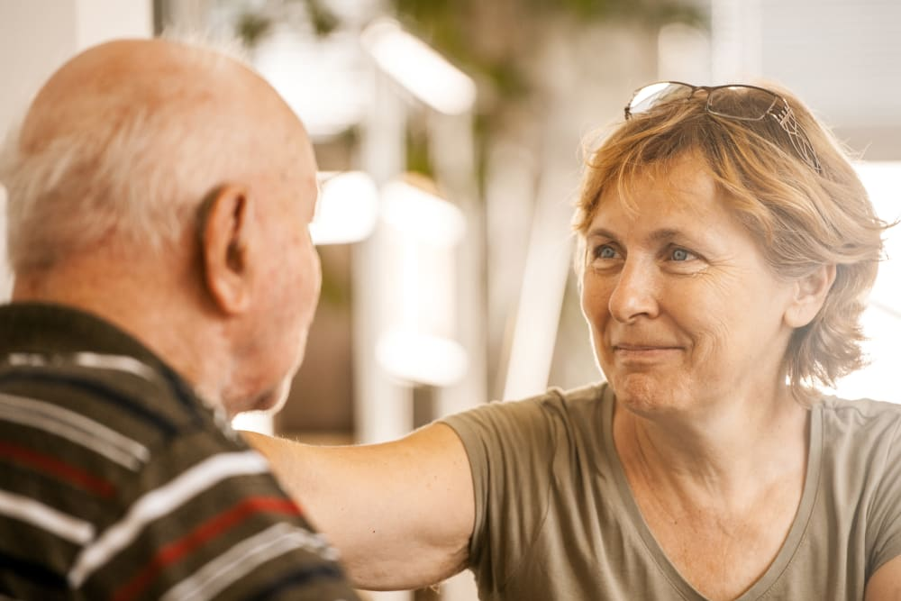 Woman visiting senior father in memory care community
