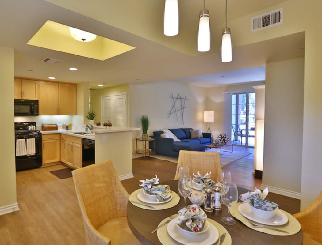 Open-concept floor plan's dining area looking into the kitchen and living area in a model home at IMT Park Encino in Encino, California