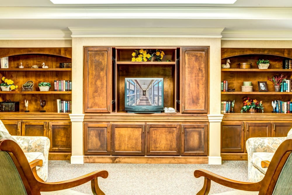 Television room with wood accents and bookshelf at Carriage Court of Washington Court House in Washington Court House, Ohio