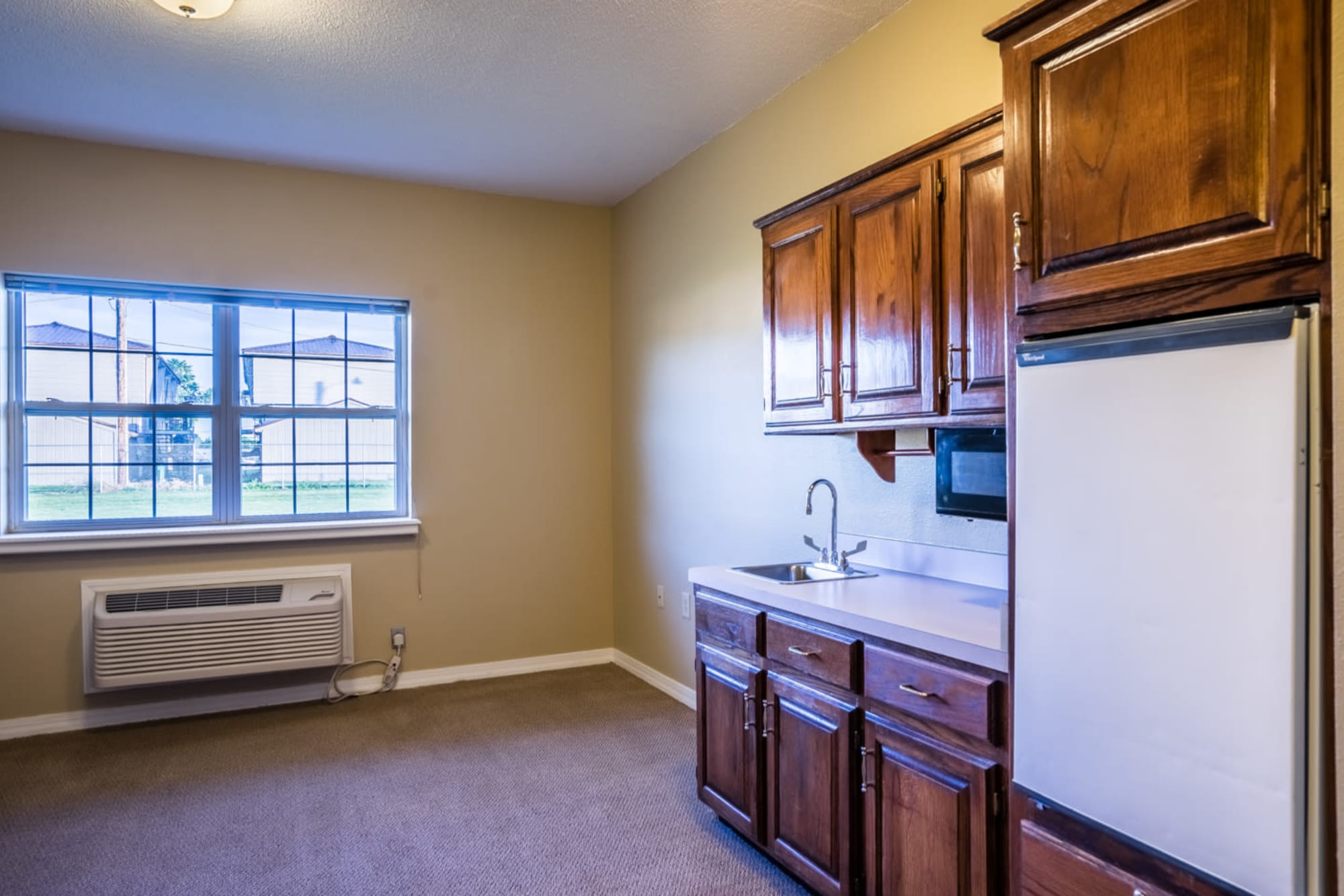 Kitchen with wood accents in senior living apartment at Madison House in Norfolk, Nebraska