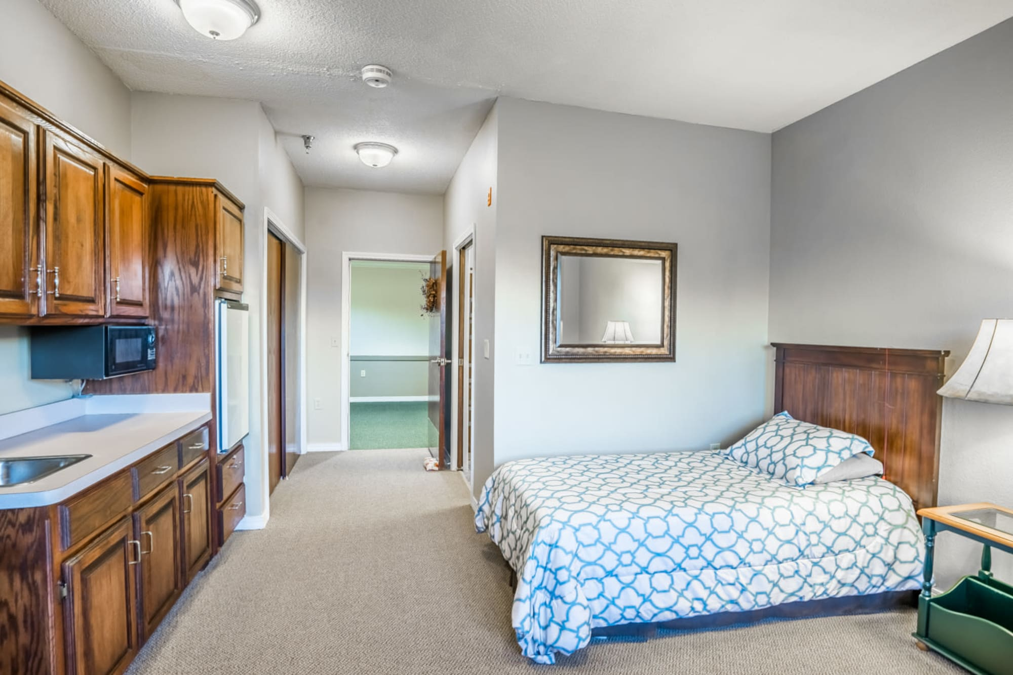 Serene bedroom with wood accent kitchen at Madison House in Norfolk, Nebraska