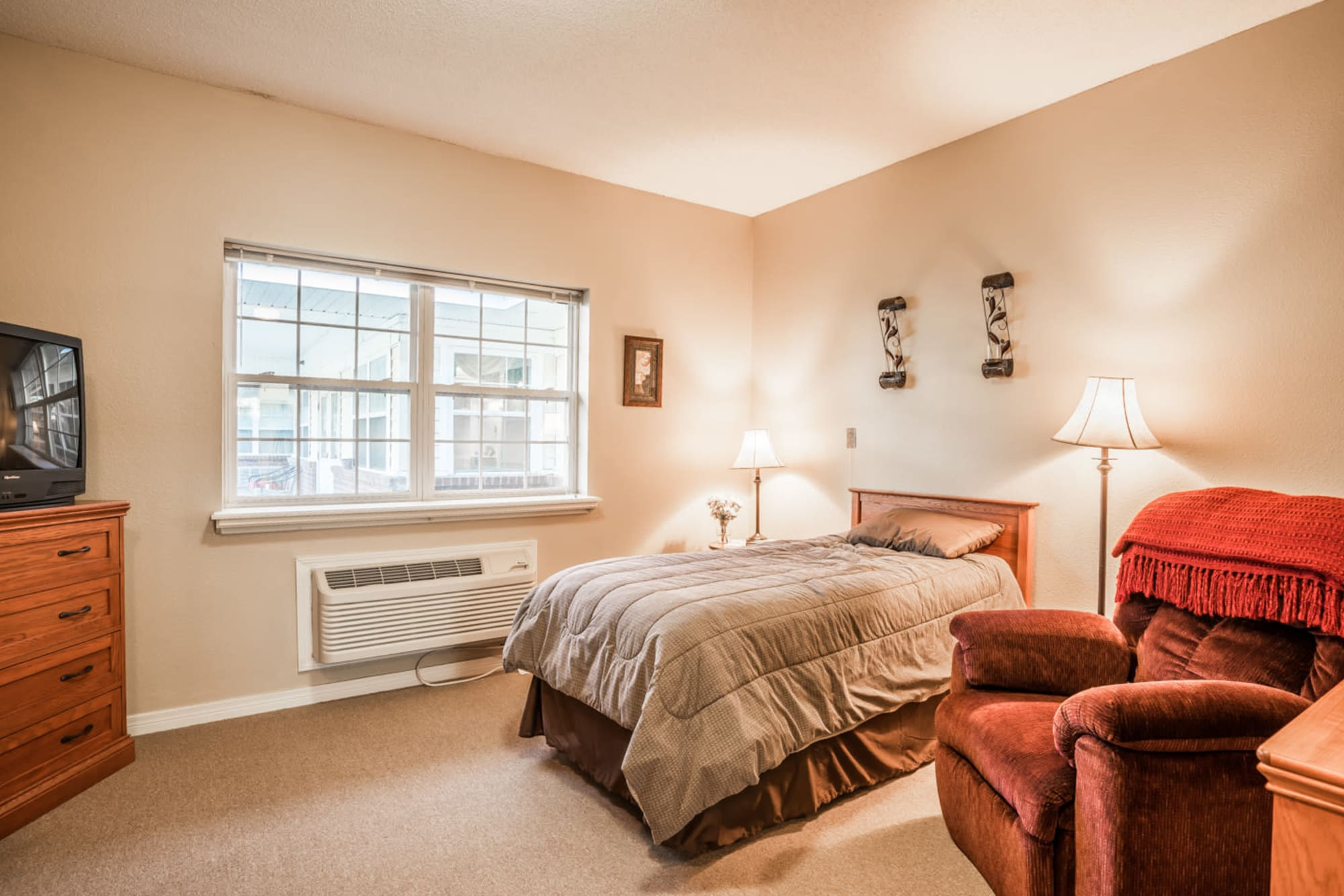 Serene bedroom area with cozy bed and armchair at Saunders House in Wahoo, Nebraska