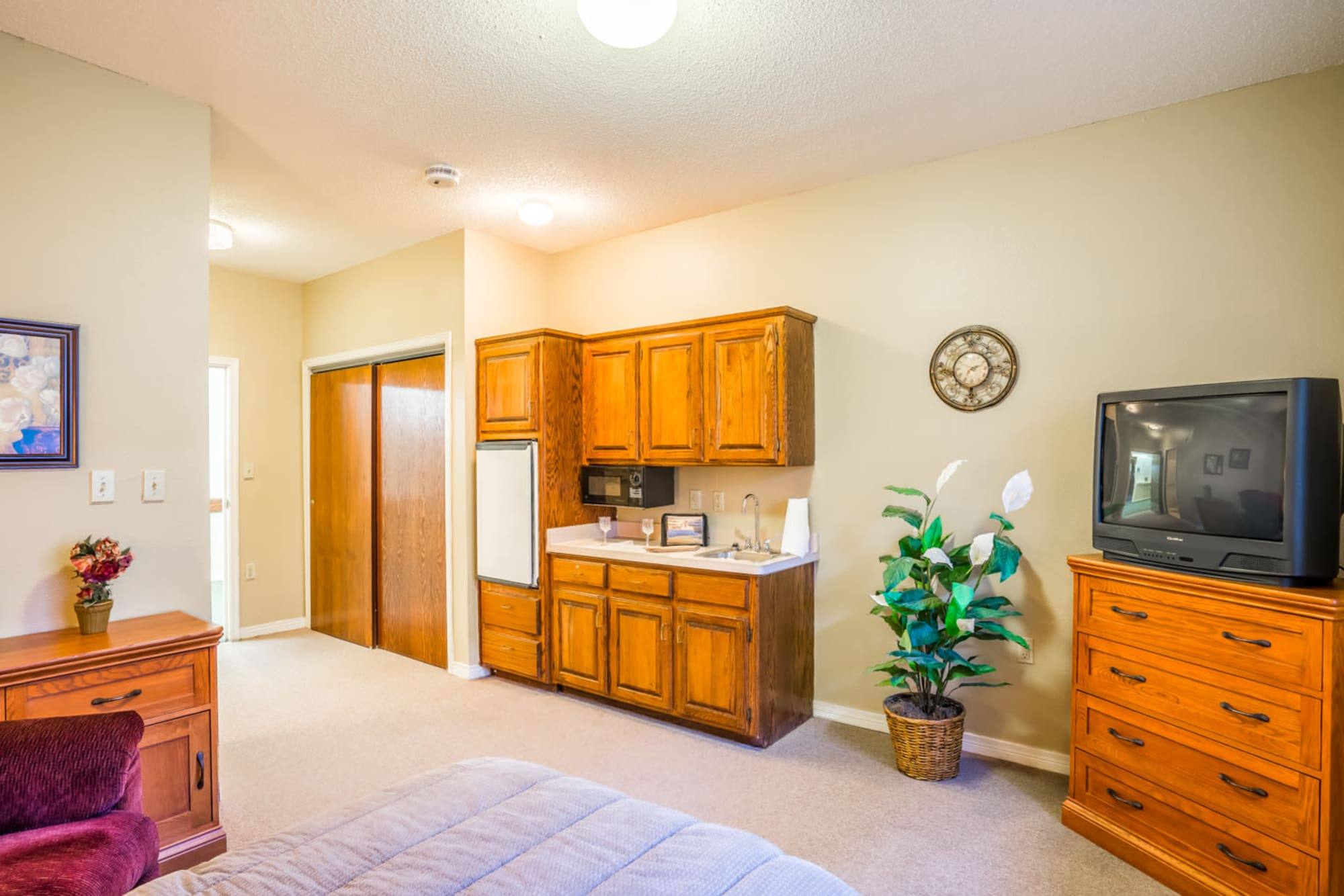 Inside of senior living apartment complete with wood cabinets and television set at Saunders House in Wahoo, Nebraska