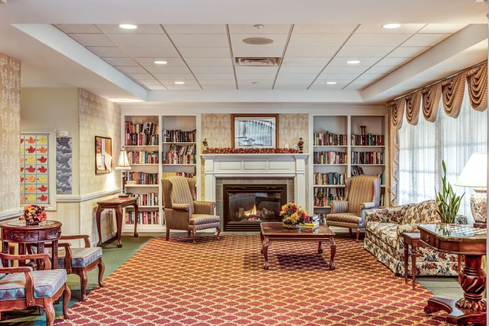 Comfortable seating area with amble bookcases and inviting fireplace at Grand Victorian of Sycamore in Sycamore, Illinois