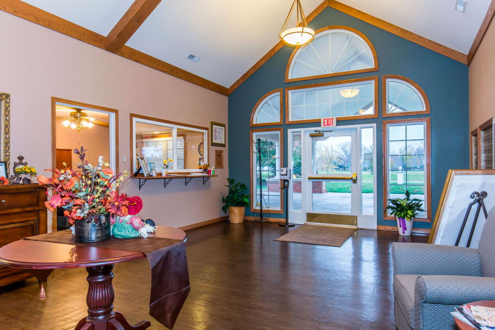 Front entryway with hardwood floors, seating, and flowers at Brookstone Estates of Rantoul in Rantoul, Illinois