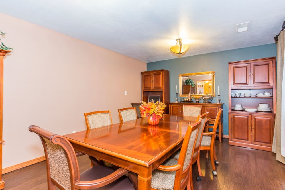 Dining room with wood table and bright lighting at Brookstone Estates of Rantoul in Rantoul, Illinois