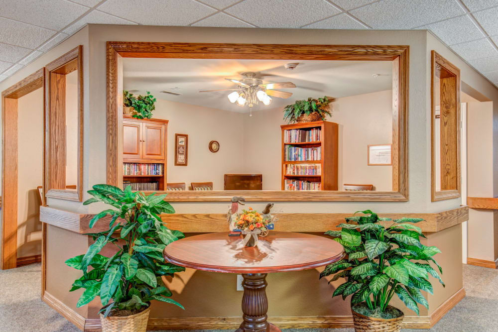 Lounge with bright lighting, foliage, and wood accents  at Brookstone Estates of Rantoul in Rantoul, Illinois