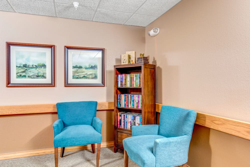 Well lit library area with vibrant blue chairs at Brookstone Estates of Olney in Olney, Illinois
