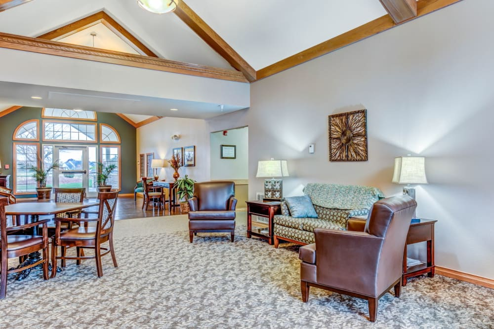 Lounge area with armchair seating and bright lighting at Brookstone Estates of Olney in Olney, Illinois