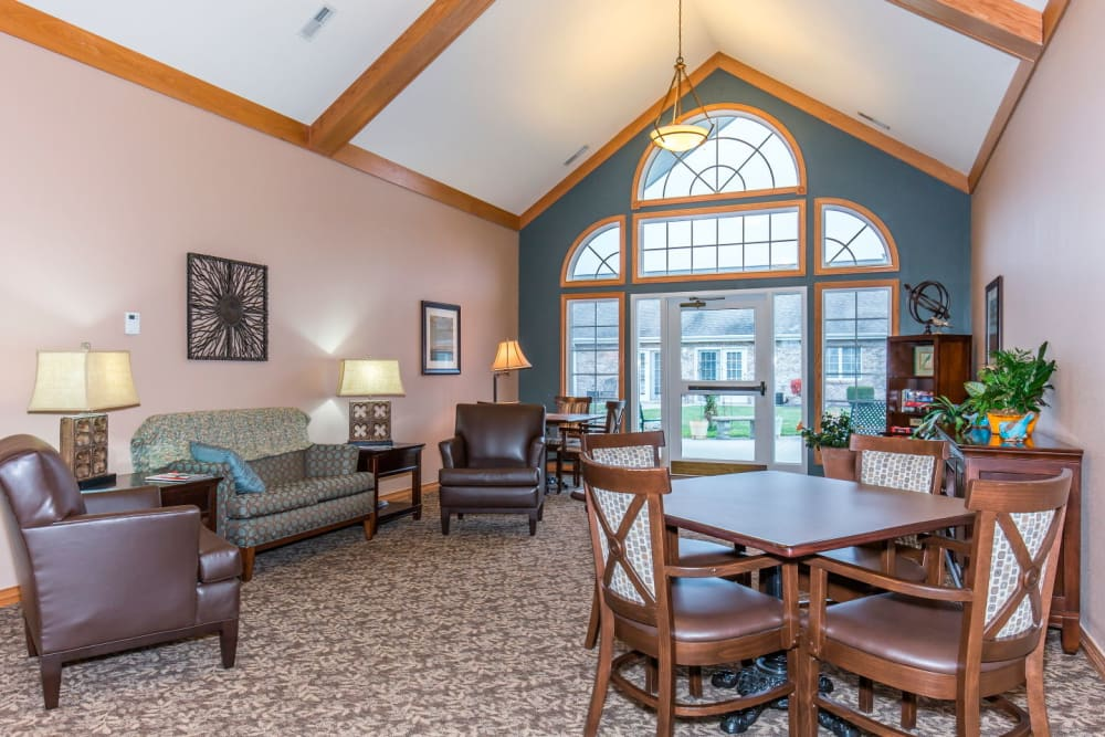 Sitting room with large window and wood table at Brookstone Estates of Olney in Olney, Illinois
