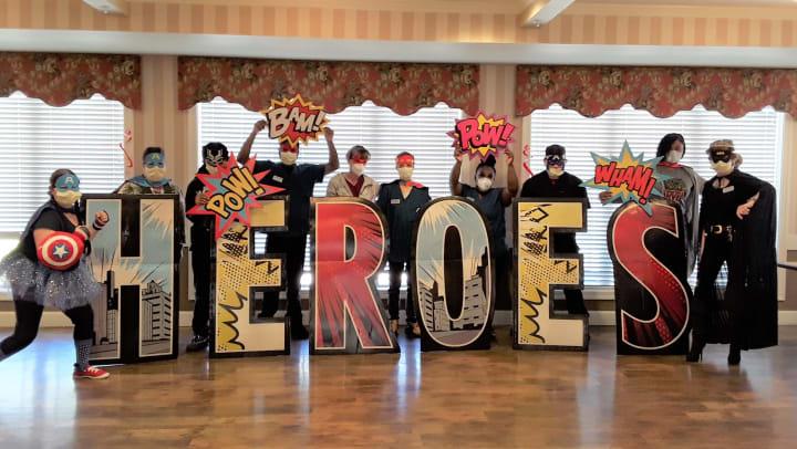 jea senior living community team posing as super heroes