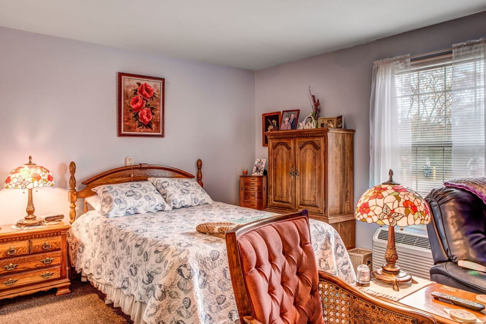 Plush bedroom at upscale senior living facility with lush bed and warm inviting wood accents at Carriage Court of Grove City in Grove City, Ohio
