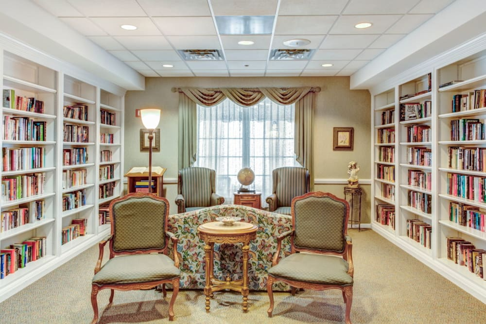 Communal reading area with wood bookshelves and bright lighting at Grand Victorian of Rockford in Rockford, Illinois