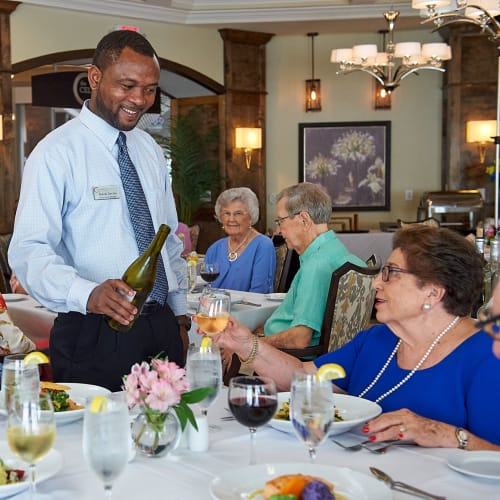A staff member pours a glass of wine for a resident in the dining room at The Crossings at Eastchase in Montgomery, Alabama
