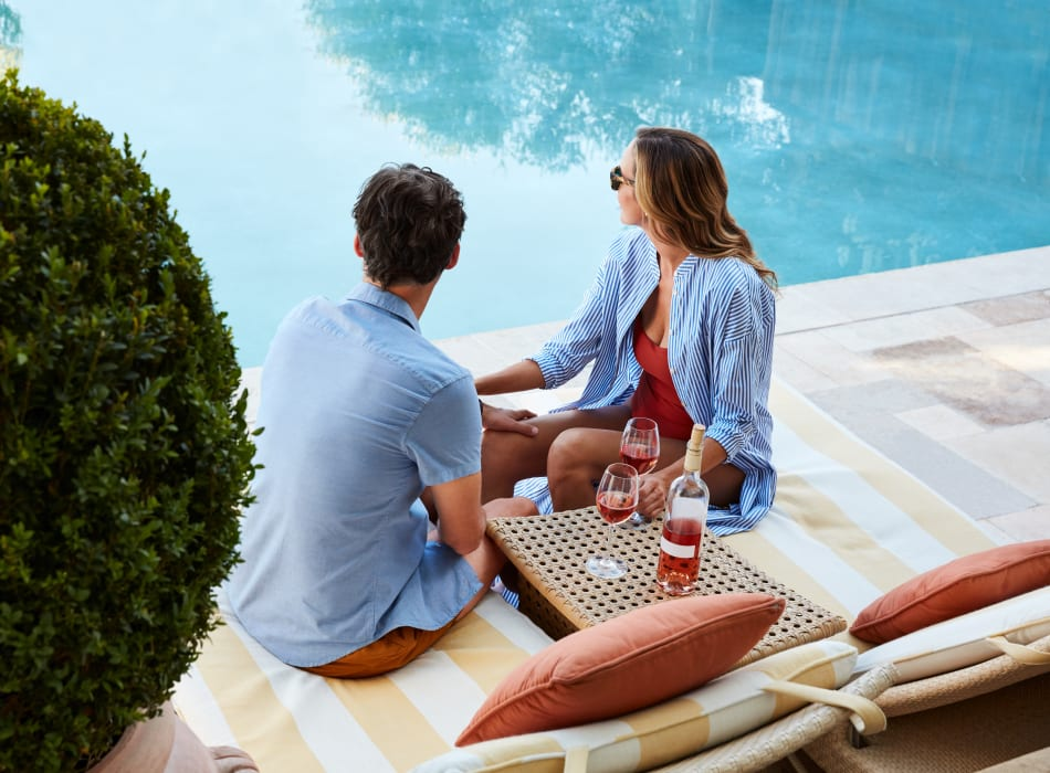 Resident couple enjoying a glass of wine near the pool at Sofi Gaslight Commons in South Orange, New Jersey