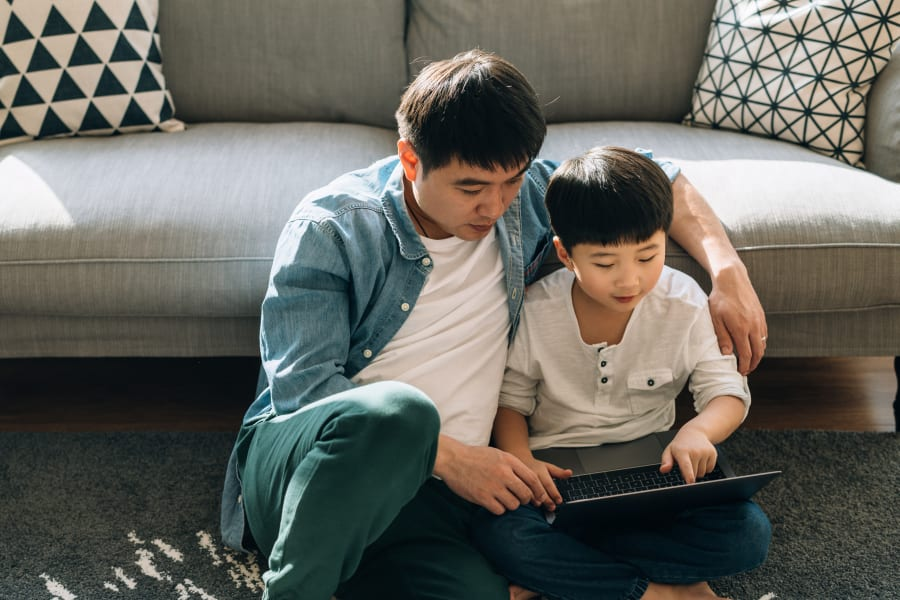 Resident student doing some homework on his laptop with help from his dad in their home at Vue Fremont in Fremont, California