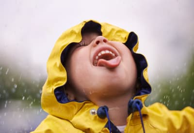 Kid playing in the rain at Westport Apartments in Angleton, Texas