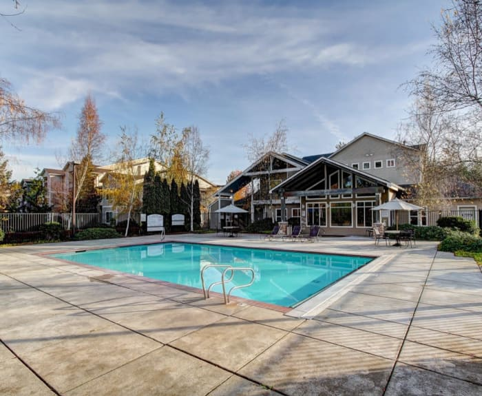 Inviting swimming pool on a beautiful day at River Trail Apartments in Puyallup, Washington