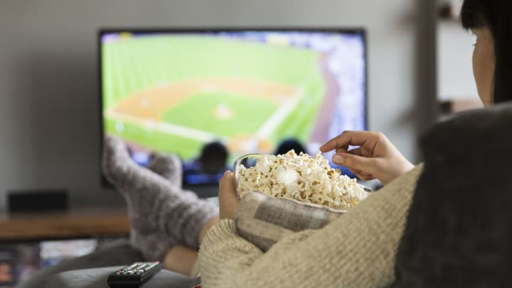 A woman sitting on a couch eating popcorn and watching a baseball game.