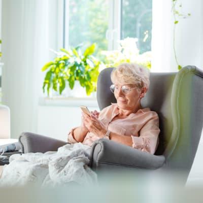 Resident sitting in a lounge chair inside Ebenezer Ridges Campus in Burnsville, Minnesota