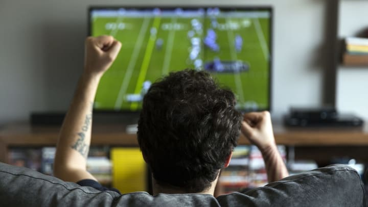 A man in the foreground cheering. In the background is a TV playing a football game.