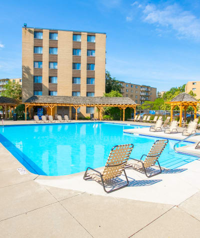 Swimming pool with building at The Drake Apartments in Mayfield Heights, OH