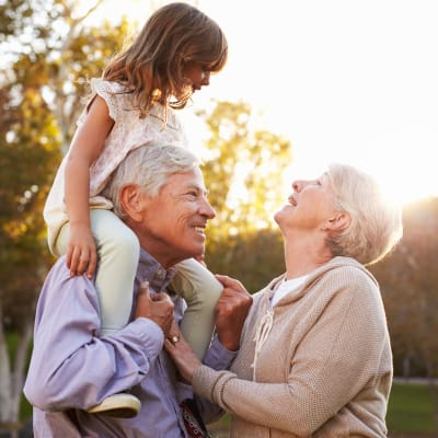 Grandparents playing with their granddaughter outdoors at Westminster Memory Care in Lexington, South Carolina