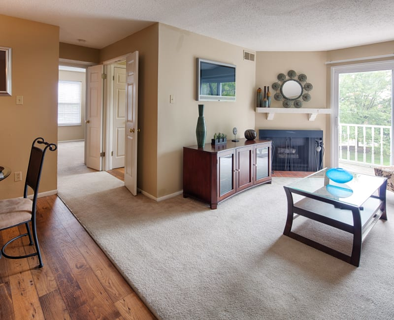 Spacious open-concept layout with plush carpeting and hardwood flooring in a model home at Oxford Hills in St. Louis, Missouri