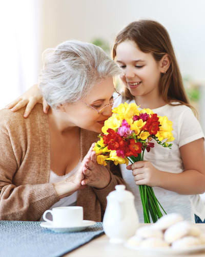 resident smelling flowers picked by her grandchild at Garden Place Senior Living